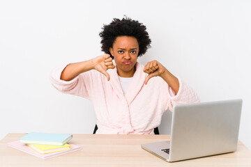 Middle aged african american woman working at home isolated showing thumb down and expressing dislike.