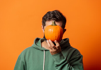 guy in face mask and green hoodie with pumpkin
