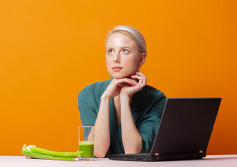 stylish blonde sits at the table next to celery juice and laptop computer