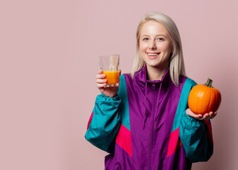 blonde woman in 90s tracksuit with pumpkin juice in glass on pink background