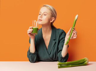 stylish blonde sits at the table next to celery juice
