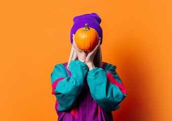 Style woman in 90s tracksuit with pumpkin