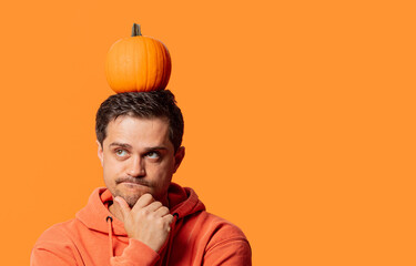 guy in a hoodie with pumpkin on his head is thinking about something