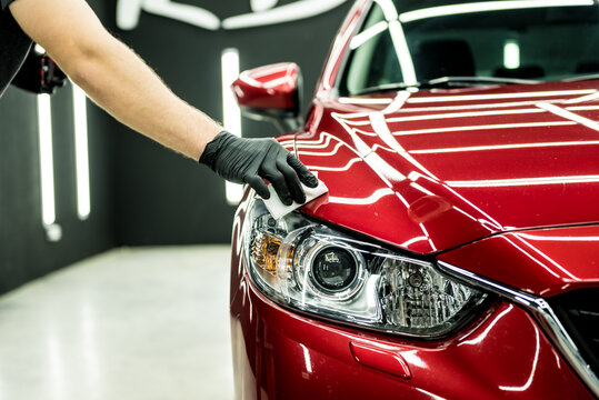 Car service worker applying nano coating on a car detail.