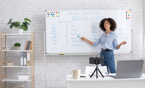 English teacher online at home. Portrait of african american woman, writing on board in classroom
