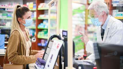 Senior pharmacist dealing with a customer, both of them wearing masks due to coronavirus
