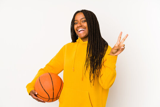 Young african american woman playing basketball isolated joyful and carefree showing a peace symbol with fingers.