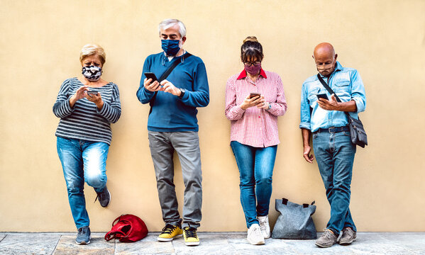 Senior people using mobile smart phone with face mask covered - Retired friends sharing content on smartphone - New normal lifestyle concept about always connected adults - Vivid pastel filter