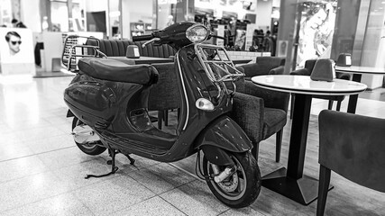 Black and white photo on the background of a shopping center. Classic scooter on the background of an empty cafe. Vintage background. Vintage style.