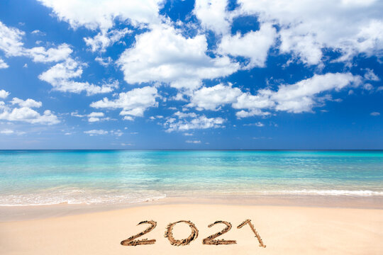 2021 written on sandy beach
