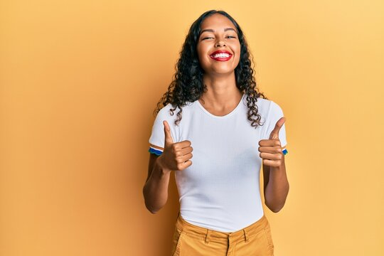 Young african american girl wearing casual clothes success sign doing positive gesture with hand, thumbs up smiling and happy. cheerful expression and winner gesture.