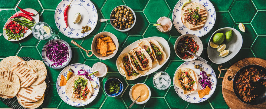 Family or friends home taco party. Flat-lay of Mexican traditional dishes Tacos with beef meat, corn tortillas and tomato salsa over green tile table background, top view. Mexican cuisine concept