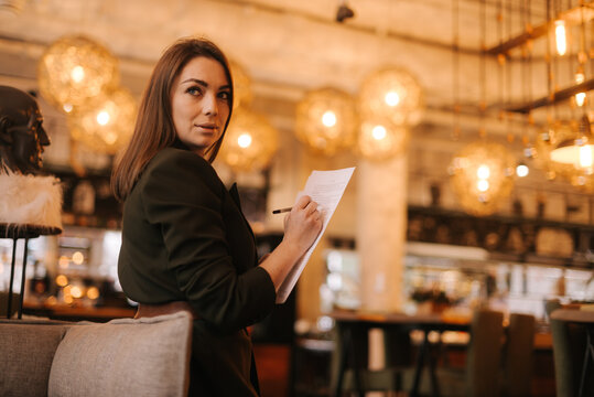 Business young woman wearing stylish formal clothes in modern luxury restaurant holding paper documents and pen in her hands. Business lady lady in suit posing in cafe.