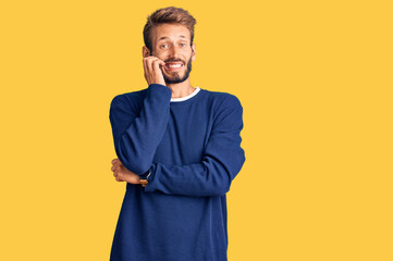 Handsome blond man with beard wearing casual sweater looking stressed and nervous with hands on mouth biting nails. anxiety problem.