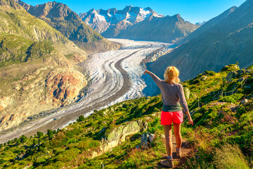 Aletsch Glacier from Moosfluh viewpoint in summer, Valais Canton, Switzerland, Europe. Tourist hiker woman pointed the Alpine glacier. Outdoor activities. Trekking in Swiss Alps.