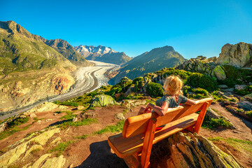 Aletsch Glacier from Moosfluh viewpoint in summer with clear blue sky in Swiss Alps, Valais Canton, Switzerland, Europe. Tourist woman relaxes sitting in a wooden bench looking over glacier.