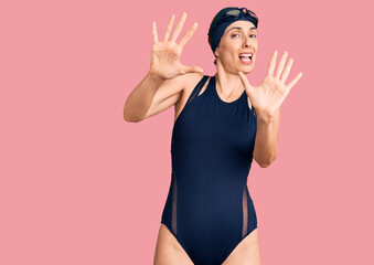 Young beautiful hispanic woman wearing swimwear and swimmer glasses afraid and terrified with fear expression stop gesture with hands, shouting in shock. panic concept.