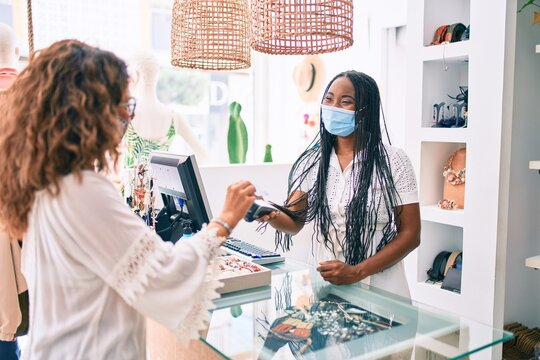 Young african american shopkeeper woman wearing medical mask working at clothing store