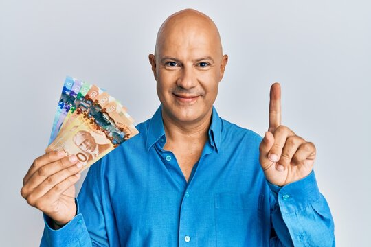 Middle age bald man holding canadian dollars smiling with an idea or question pointing finger with happy face, number one