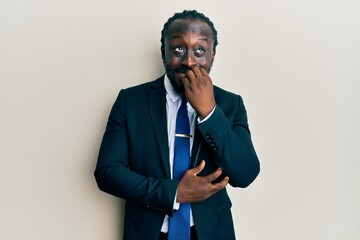 Handsome young black man wearing business suit and tie looking stressed and nervous with hands on mouth biting nails. anxiety problem. Fotobehang