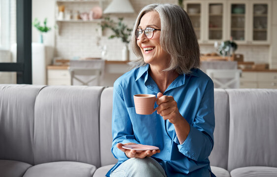 Happy beautiful relaxed mature older adult grey-haired woman drinking coffee relaxing on sofa at home. Smiling stylish middle aged 60s lady enjoying resting sitting on couch in modern living room.