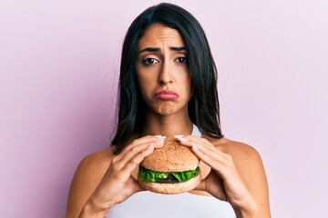 Beautiful hispanic woman eating a tasty classic burger depressed and worry for distress, crying angry and afraid. sad expression.
