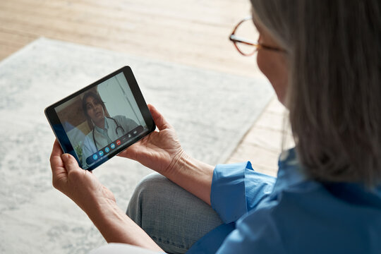 Over shoulder closeup view of old woman patient video calling virtual doctor using tablet at home. Online telemedicine chat meeting. Seniors ehealth, telehealth consultation, tele medicine concept.