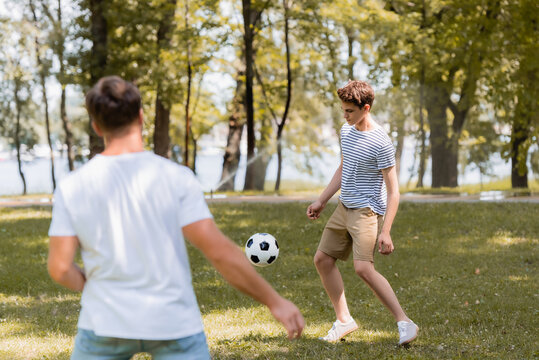 selective focus of teenager boy playing football with father