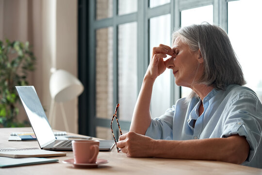 Tired old senior business woman taking off glasses suffers from eyestrain, stress, headache, fatigue after computer use work in office. Exhausted sick mature lady feels eye strain problem at workplace