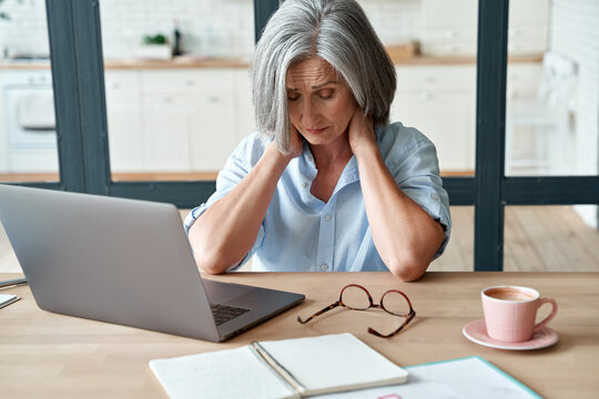 Tired stressed old mature business woman suffering from neckpain working from home office sitting at table. Overworked senior middle aged lady massaging neck feeling hurt pain from incorrect posture.