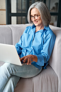 Happy 60s older mature middle aged adult woman holding laptop using computer sitting on couch at home. Smiling elegant senior grey-haired lady spending time with technology device in living room.