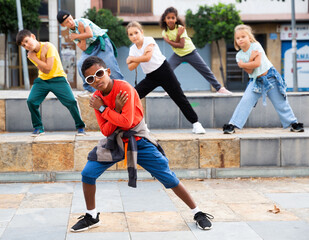 Little boy hip hop dancer exercising with friends at open air dance class