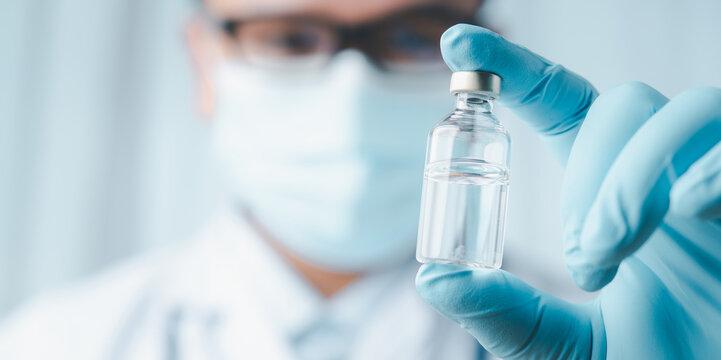 Development and creation of coronavirus vaccine COVID-19 .Coronavirus Vaccine concept in hand of doctor blue vaccine jar. Vaccine Concept of fight against coronavirus.