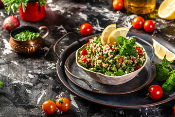 Tabbouleh salad. Middle eastern or arab dish. Levantine vegetarian salad with parsley, mint, bulgur, tomato. Vegan food. Top view