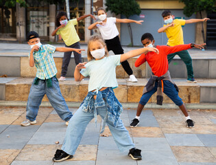 Girls and boys hip hop dancers in protective face masks doing dance workout during open air group...