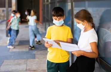 Tweenage schoolchildren in protective masks friendly talking near school building in warm autumn day. New life reality during coronavirus pandemic