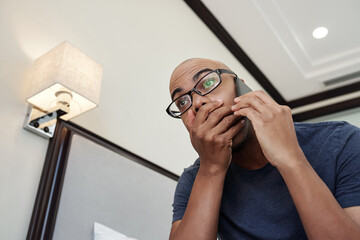 Black man receiving shocking news on the phone and covering mouth with hand from excitement