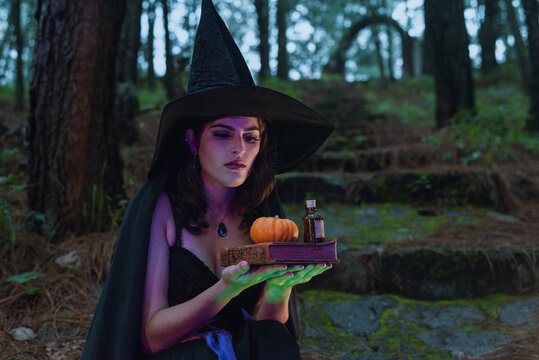 Halloween witch young girl wicca wearing black costume witches holding a old book for a spells and pumpkin in a dark forest  with magic lights