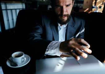 business man in suit in cafe in front of laptop with a cup of drink official Fotobehang