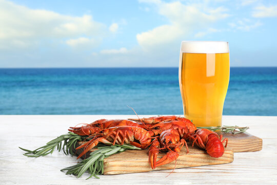 Cooked crayfishes served with beer on white wooden table near sea