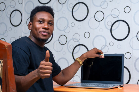 young black man gives a thumbs up as he tapes of his computer webcam