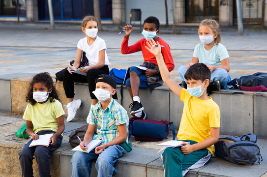 Multiethnic group of preteen schoolchildren in protective masks learning with workbooks in schoolyard in warm autumn day. Back to school concept after lockdown