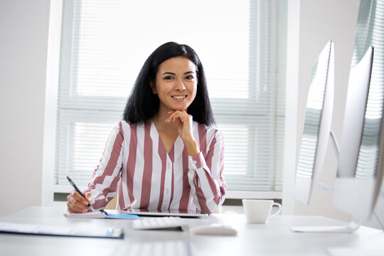 Portrait of hispanic business woman looking at camera at workplace in an office