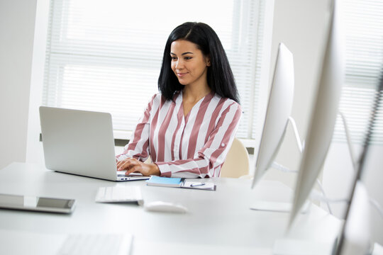 Portrait of hispanic business woman at workplace in an office