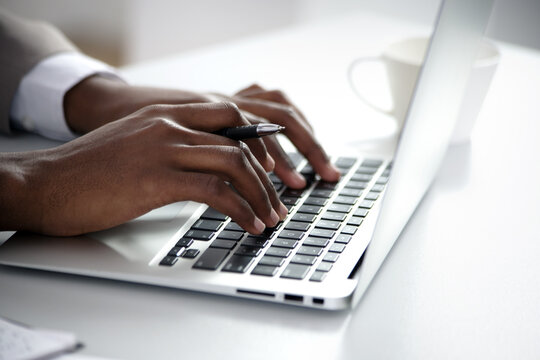 Close-up of hands of african american businessman typing on a keyboard.