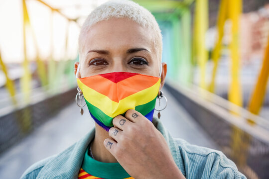 Young woman wearing gay pride mask - Lgbt rights, diversity, tolerance and gender identity concept