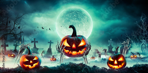 Jack O' Lantern On Skeleton Arms In Graveyard At Night - Halloween With Full Moon