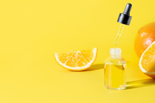 Cosmetic hyaluronic acid or hydrating oil and orange essence in glass bottle with flying pipette on yellow background with copy space for design.