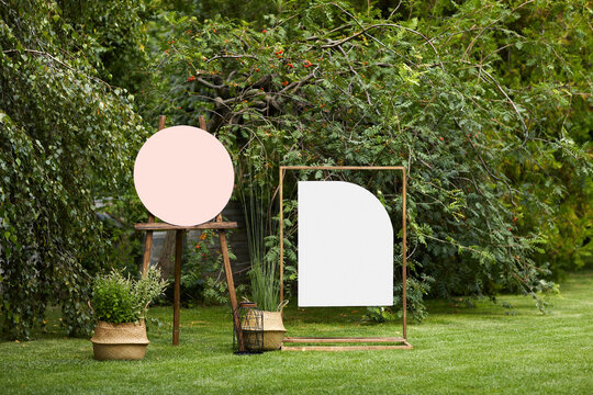 empty board stands on green lawn on wedding. invitation for guests for summer wedding ceremony