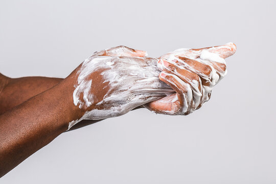 Black african american man washing hands isolated on white background. Hygiene, cleanliness concept.